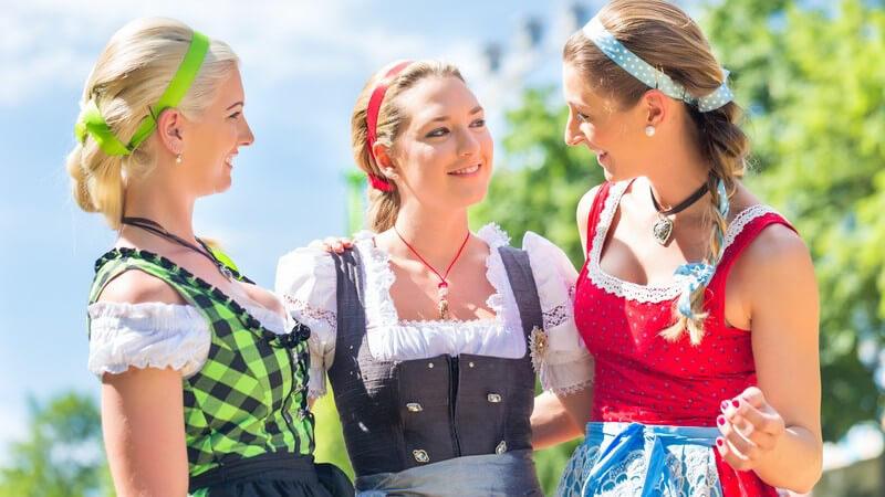 Drei junge Frauen in farbenfrohen Dirndln unterhalten sich im Grünen