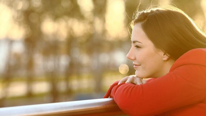 Junge Frau in roter Jacke lehnt bei Sonnenuntergang auf einem Geländer und blickt nachdenklich ins Leere