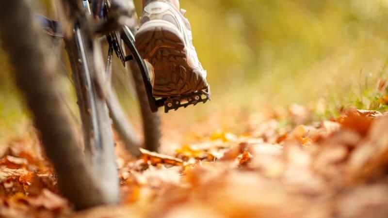 Fuß auf dem Pedal eines Mountainbikes im Laub