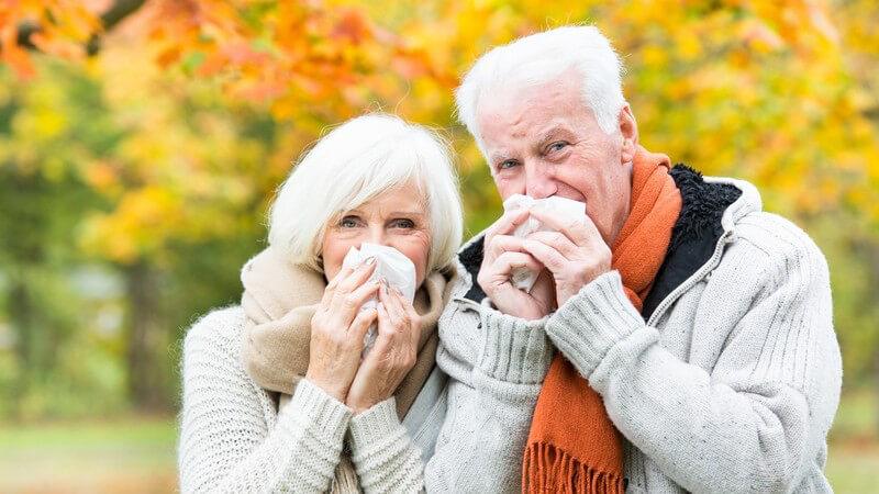 Erkältetes Seniorenpaar putzt sich im herbstlichen Park die Nase