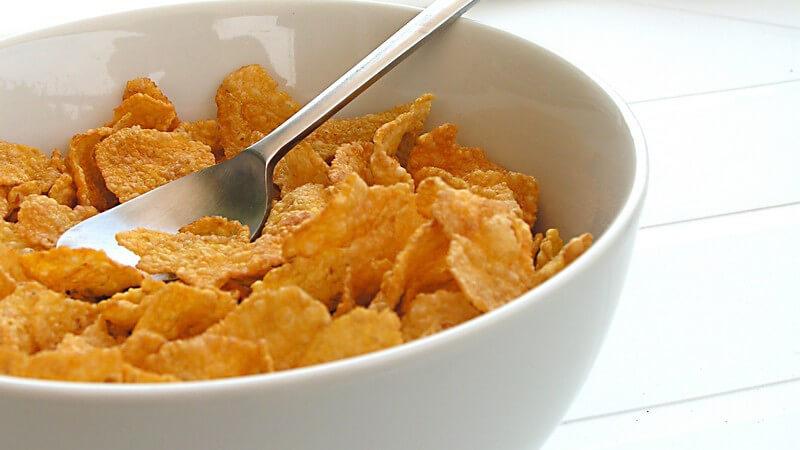 Weiße Schale mit Cornflakes und Löffel auf weißem Tisch mit weißen Servietten