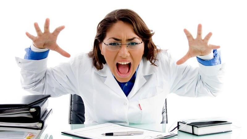 Gestresste Ärztin sitzt am Schreibtisch und schreit, Hände nach oben