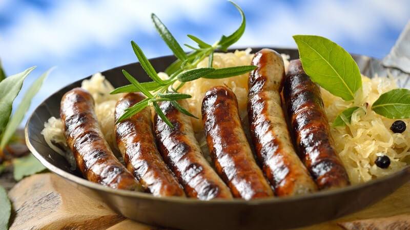 Rostbratwürste auf Sauerkraut in Eisenpfanne auf dickem Holzbrett