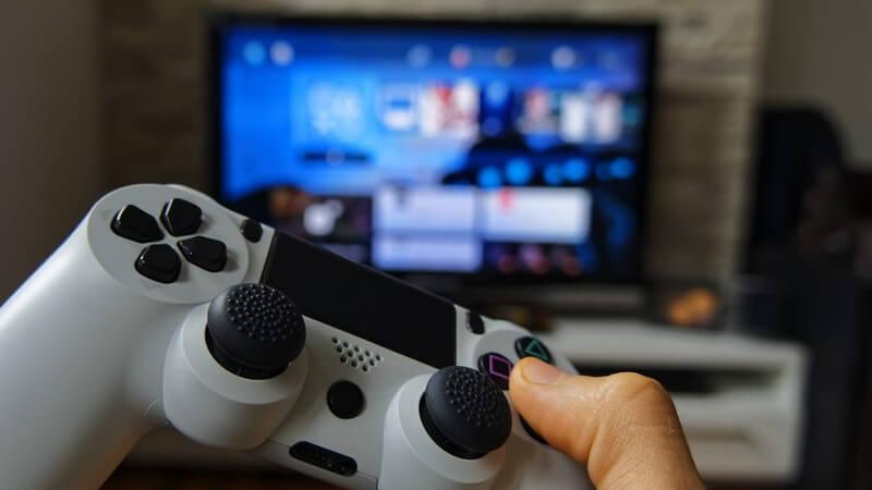 Hand mit grauem Controller einer Spielkonsole vor dem Fernseher