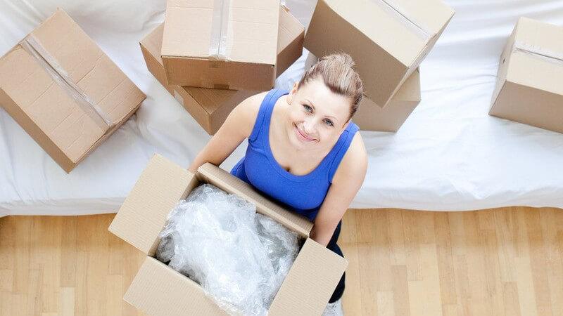 Junge Frau mit Umzugskartons in neuer Wohnung