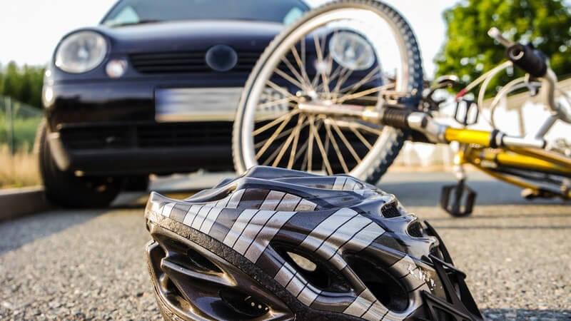 Grauer Fahrradhelm und gelbes Fahrrad liegen nach einem Unfall auf dem Asphalt vor einem Auto