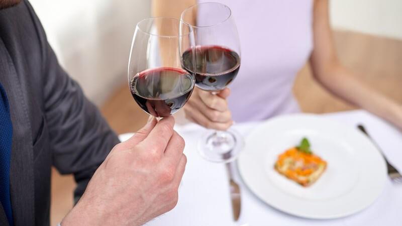 Paar beim Essen im Restaurant stößt mit Rotwein an