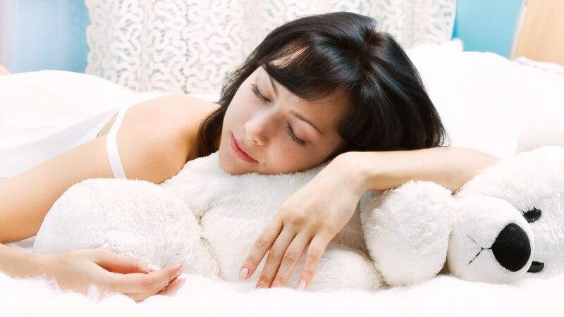 Dunkelhaarige schlafende junge Frau liegt in weißem Bett auf Kuscheltier-Eisbär in Zimmer