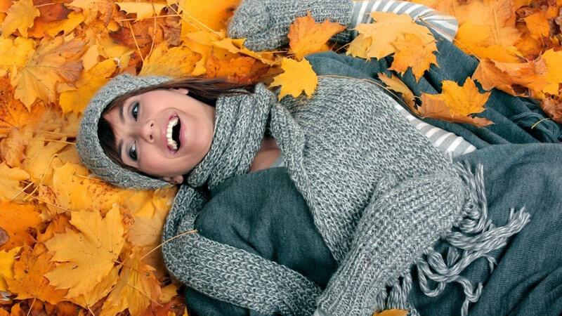 Junge Frau mit Mütze und Schal liegt auf Herbstblättern