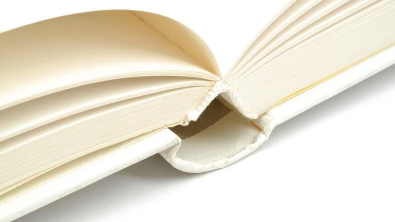 Nahaufnahme aufgeschlagenes weißes Buch auf weißem Hintergrund