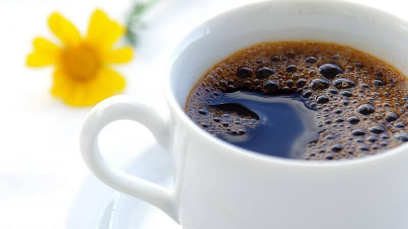 Kaffee in weißer Tasse mit gelber Blume im Hintergrund