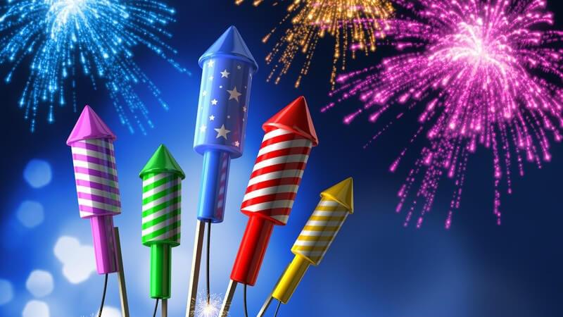 Fünf bunte Silvester-Raketen mit Feuerwerk im Hintergrund (Fotomontage)