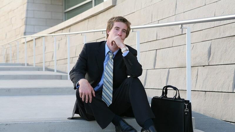 Junger Geschäfstmann im Businessoutift sitzt draußen nachdenklich mit Aktentasche auf Treppe