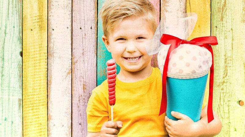 Junge in gelbem Shirt steht vor einer bunten Holzwand und hält einen Lutscher und eine Schultüte zur Einschulung