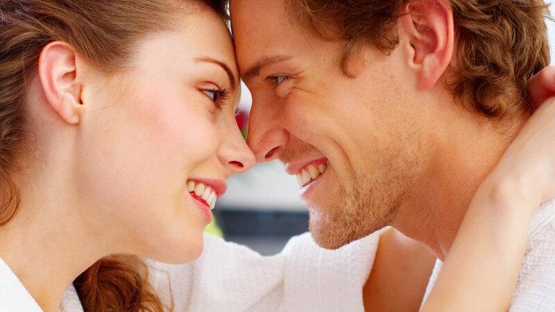 Junges Paar im Bademantel Stirn an Stirn lächelt sich verliebt an
