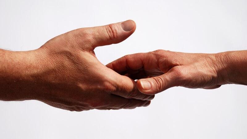 Frauen- und Männerhand kurz vor Händedruck