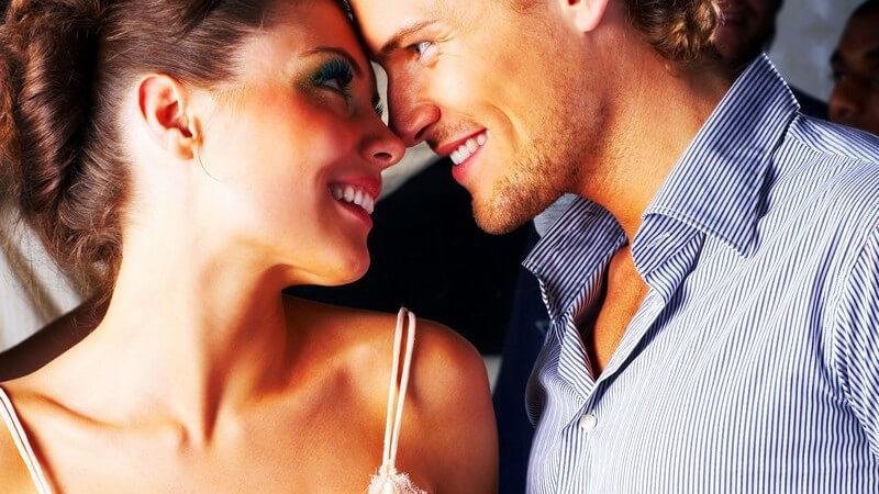 Paar in Bar an Theke, Stirn an Stirn, lächeln sich an