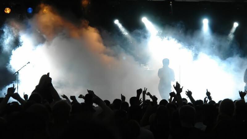 Jubelndes Publikum vor Bühne mit Musikern, Nebel