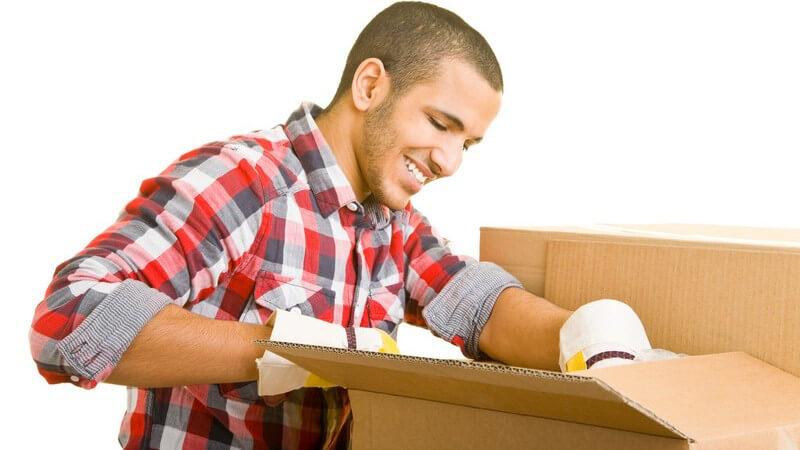 Junger Mann packt Umzugskartons