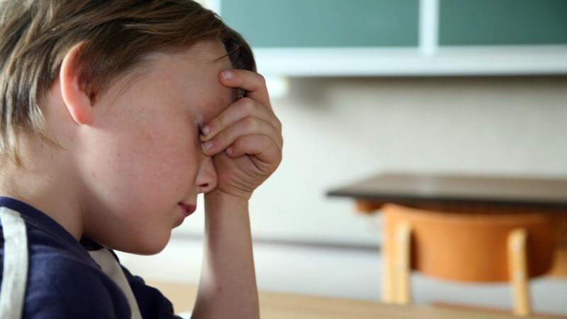 Kleiner Junge in Klassenraum hält sich Hand vor Augen