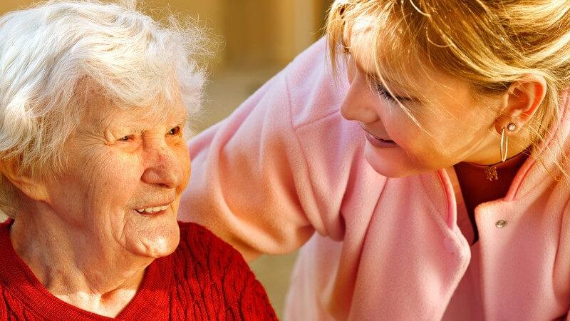 Blonde Frau in rosa Jacke beugt sich zu einer Seniorin in rotem Pullover runter