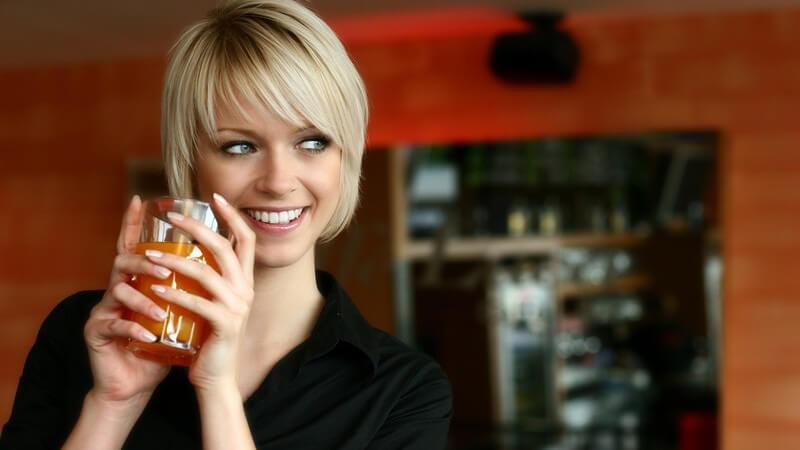 Blonde, kurzhaarige Frau mit Fruchtsaftgetränk schaut lächelnd zur Seite