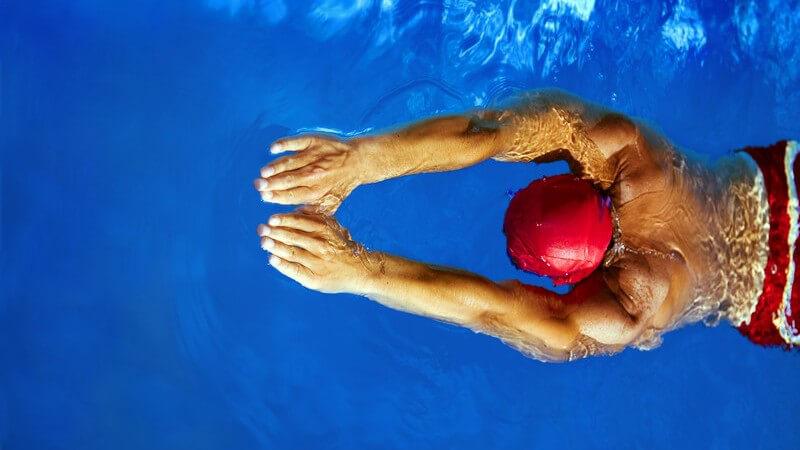 Schwimmer mit roter Badekappe und roter Schwimmshort von oben, die Arme nach vorne gestreckt