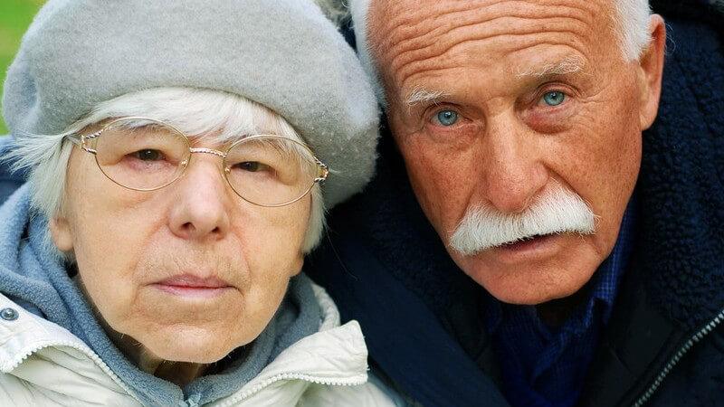 Senioren - Frau mit Brille und grauem Hut neben einem Mann mit weißem Schnurrbart