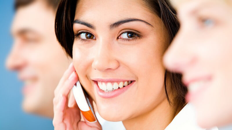 Junge Geschäftsfrau mit Handy lächelt in Kamera