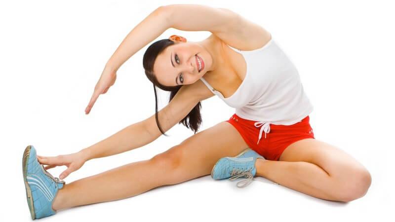 Junge Frau im Sportoutfit bei Dehnübung