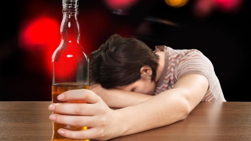 Betrunkene Frau hängt auf einem Tisch, eine Bierflasche von sich gestreckt, im Hintergrund Partylichter