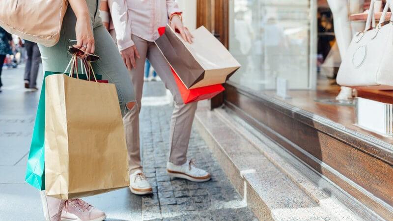 Zwei Frauen beim Shopping, stehen mit Einkaufstüten bepackt vor dem Schaufenster einer Modeboutique