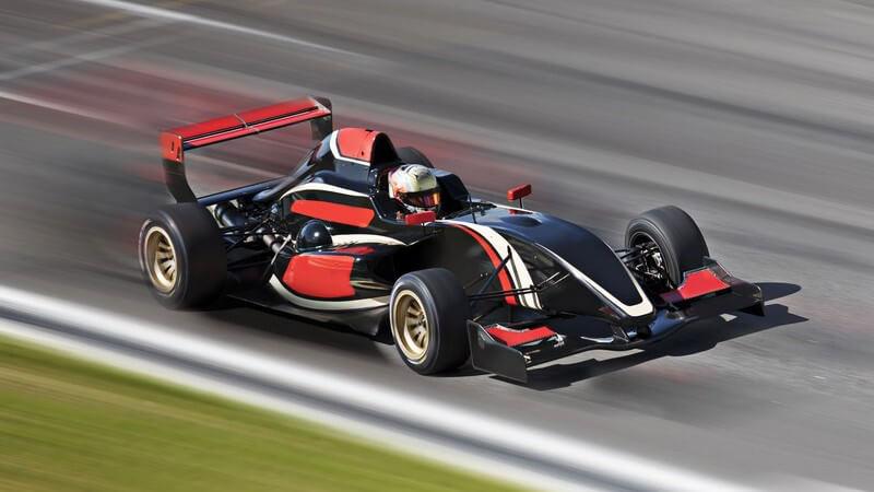 Schwarz-rotes Formel 1-Auto auf Rennstrecke