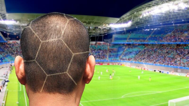 Braunhaariger Hinterkopf eines Mannes mit Fußballfrisur vor Fußballstadion