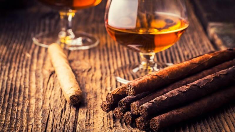 Zigarren liegen neben Cognacgläsern auf Holztisch