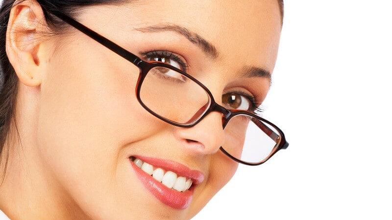 Geschäftsfrau mit dunkelbrauner Brille lächelt in Kamera