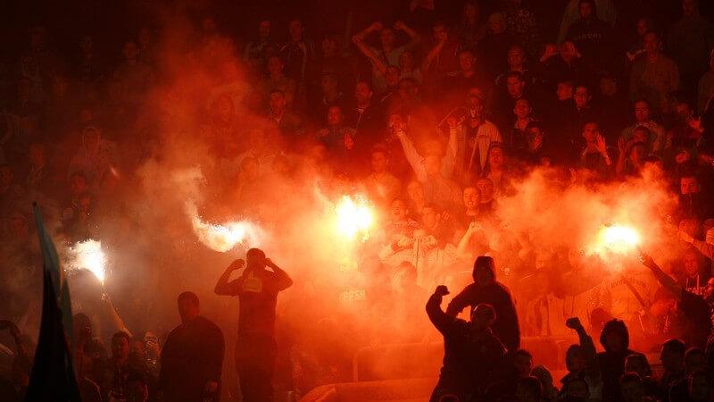 Pyrolichter bei Fußballturnier, jubelnde Fans in Menschenmenge