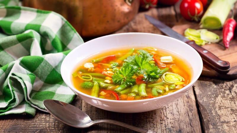 Weißer Suppenteller mit Gemüsesuppe auf Holztisch, neben Zutaten, grünem Küchenhandtuch und Kochtopf