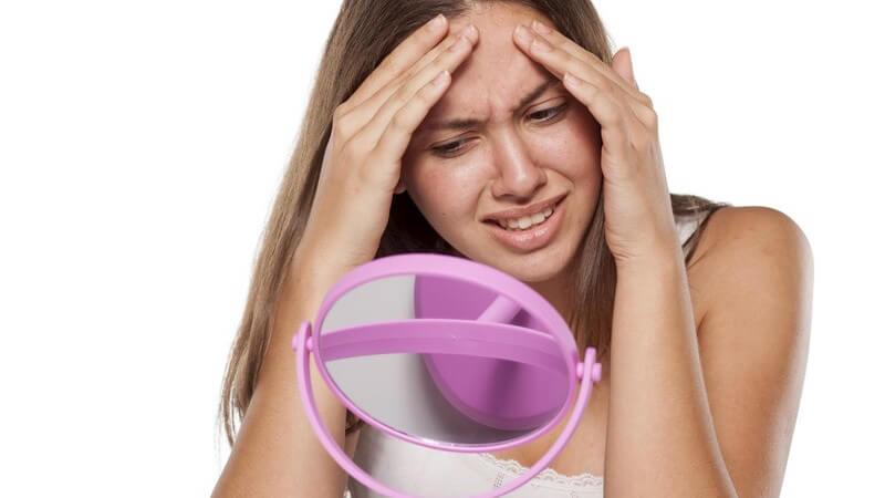 Junge Frau guckt in einen pinken Kosmetikspiegel, unglücklich über ihre Pickel an der Stirn