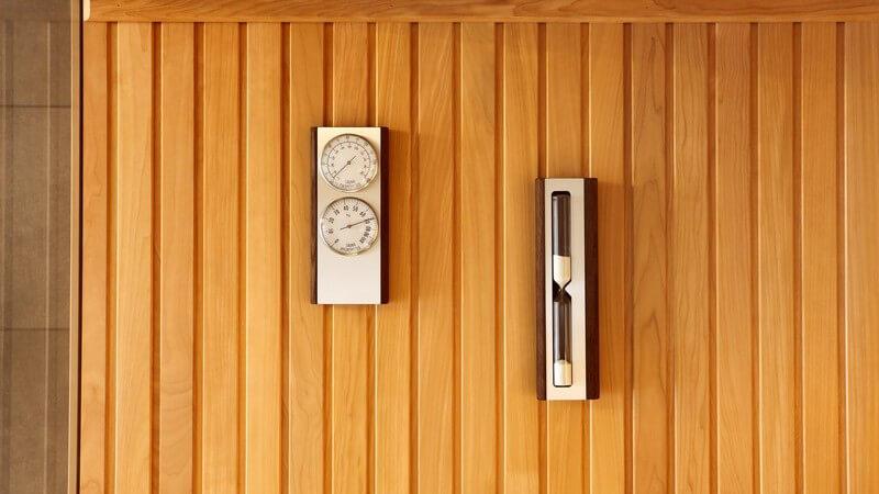 Thermometer und Sanduhr hängen an der Holzwand einer Sauna