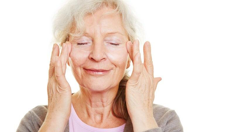 Seniorin mit langen grauen Haaren hat die Augen geschlossen und cremt ihr Gesicht ein
