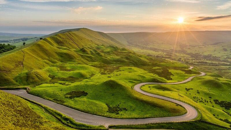 Kurvenreiche Landstraße schlängelt sich bei Sonnenuntergang durch den hügeligen Peak District in England