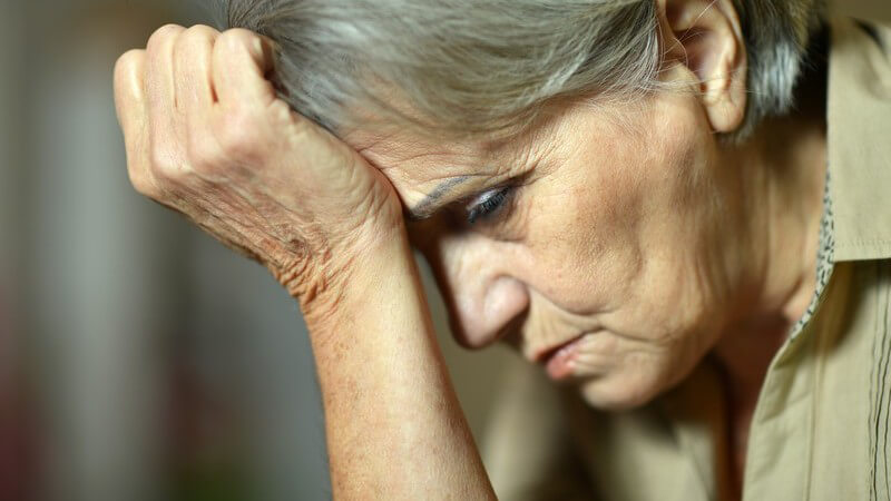 Traurige Seniorin, den Kopf ans Handgelenk gestützt