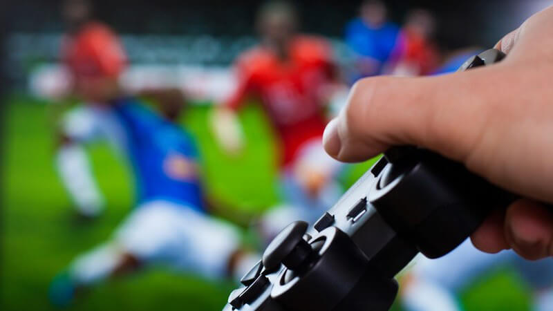 Hand mit schwarzem Gamepad vor einem Fußball-Videospiel