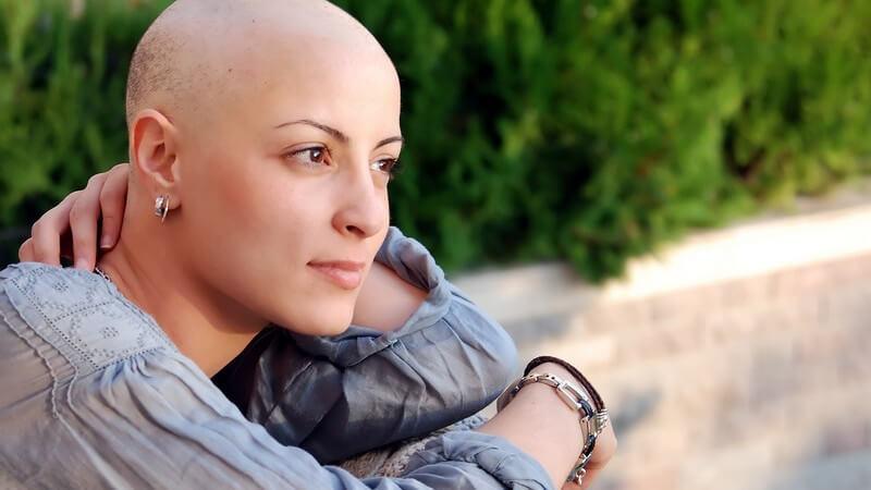 Junge krebskranke Frau mit Glatze schaut nachdenklich aber zuversichtlich in die Ferne