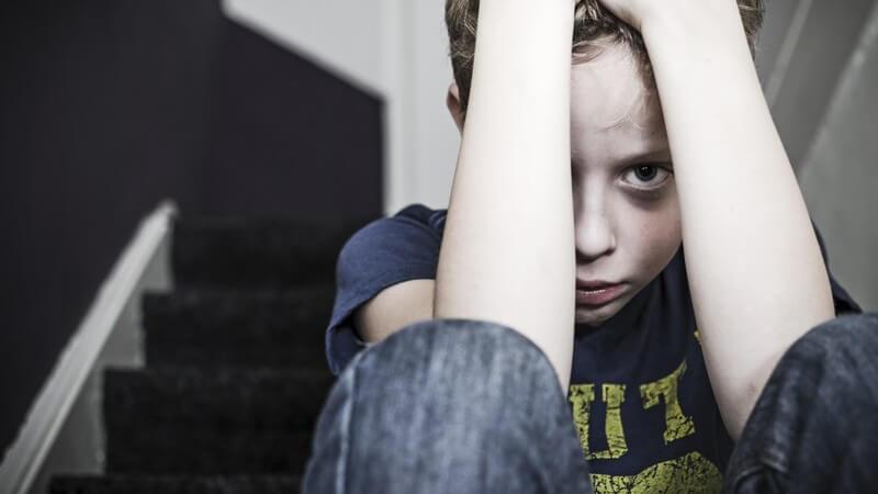 Kleiner Junge sitzt auf einer Treppe und verbirgt ängstlich sein Gesicht hinter den Armen
