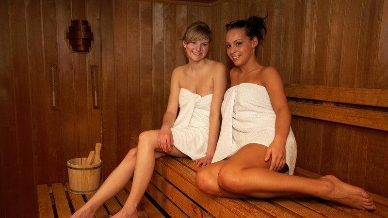Zwei junge Damen sitzen mit weißem Handtuch in der Sauna