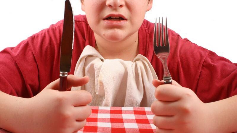 Junge sitzt mit Messer und Gabel am Tisch und wartet ungeduldig auf sein Essen