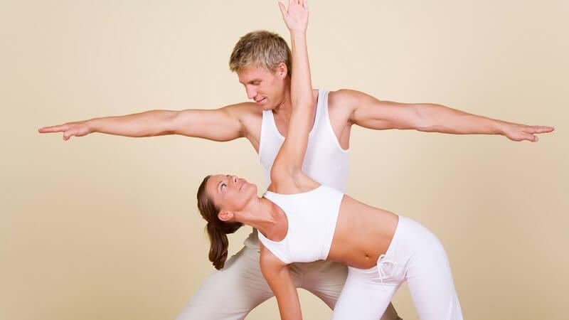 Paar in weißer Sportkleidung bei Yogaübung