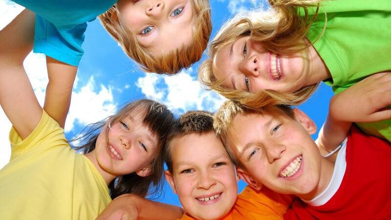 Ansicht von unten: fünf Kinder stehen im Kreis und lächeln in Kamera